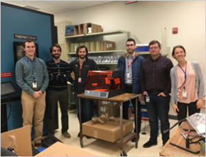 MITRE researchers and Voxel personnel installing Voxel 3D printer in MITRE's lab.